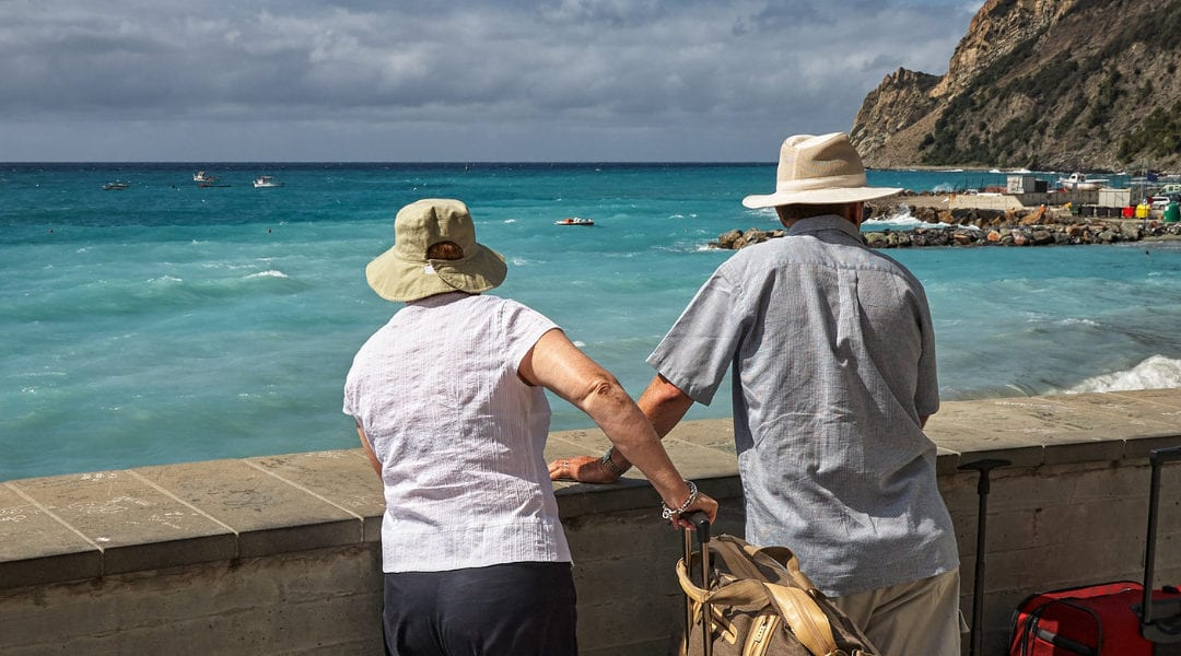 Old couple with suitcases looking over wall into ocean