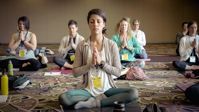 People sitting on floor practicing yoga