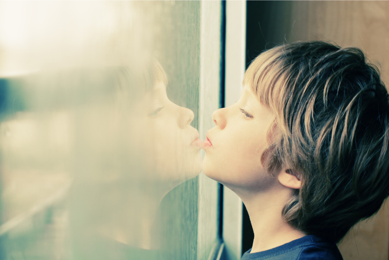 Autustic child looking out window